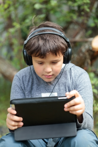 Teen boy in headphones with pad